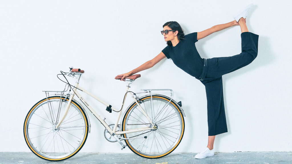 A woman wearing a navy blue top and capri pants stretches while holding onto the seat of a white bicycle.