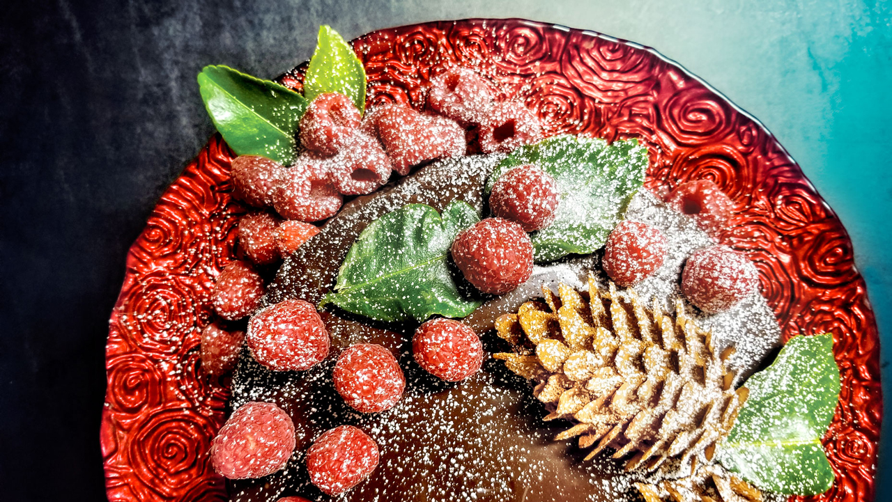 A chocolate tart decorated with raspberries, pinecones, and leaves