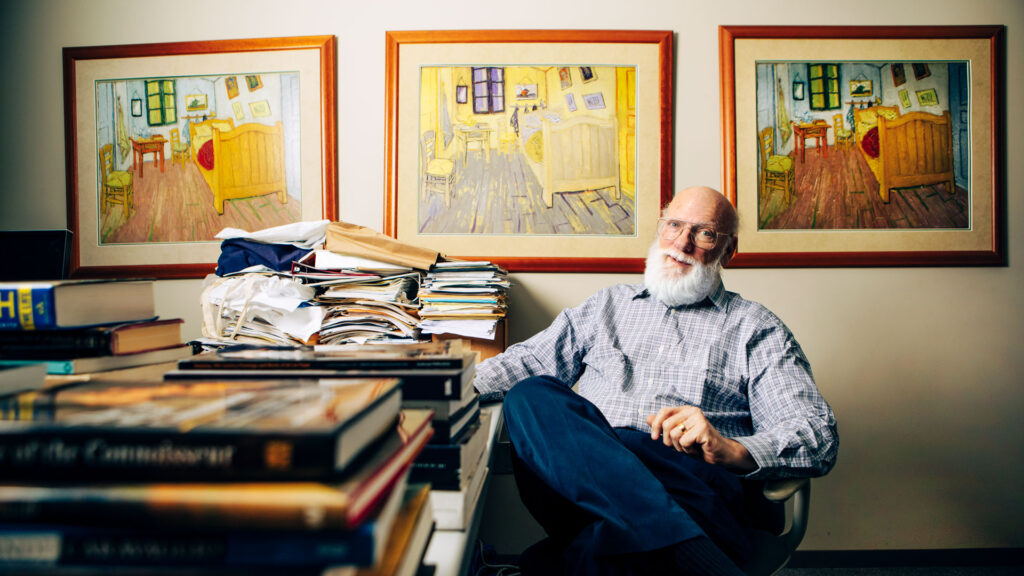 Professor Rick Johnson seated in his office in front of three versions of a painting of Van Gogh's bedroom at Arles.
