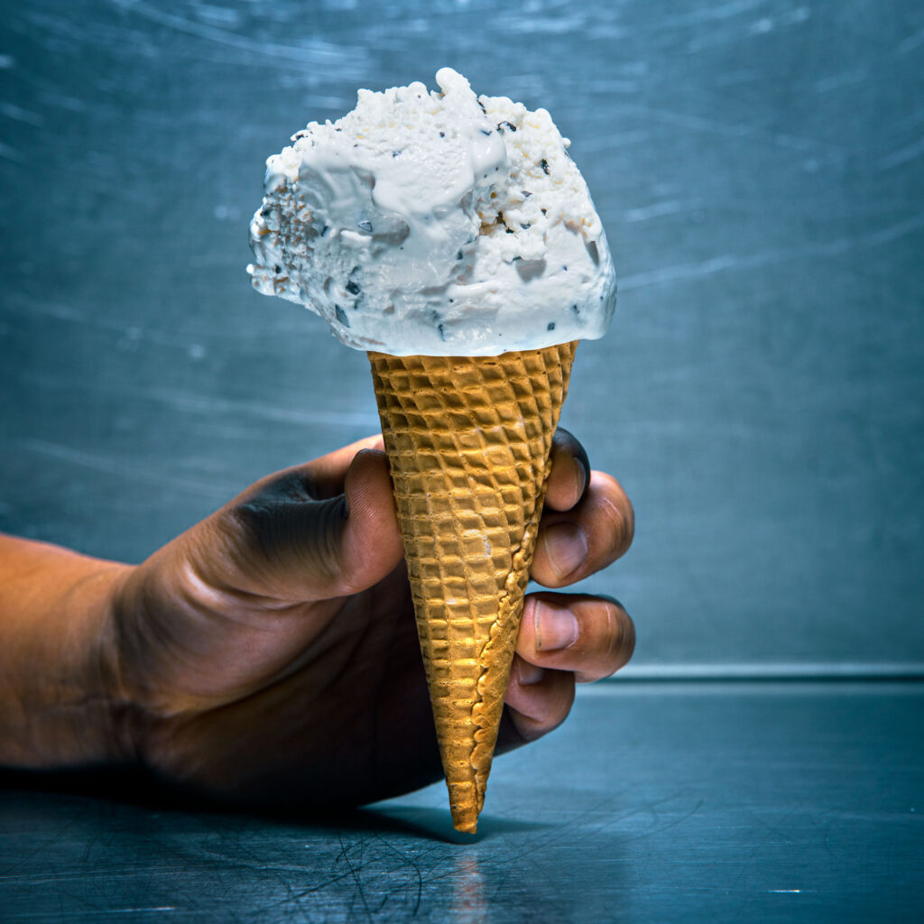 A hand holding an ice cream cone containing a scoop of vanilla ice cream with chocolate flakes.