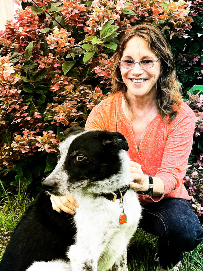 Dr. Pamela Perry with a black and white dog.