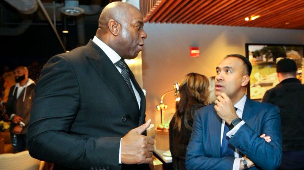 Magic Johnson (left) and Tatum speaking to each other.