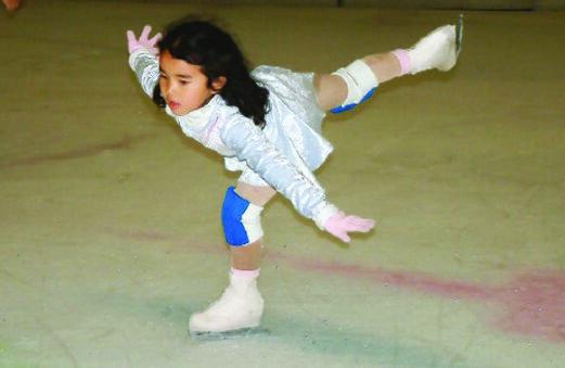 Karen Chen as a child in a light blue skating dress, practicing a spiral.