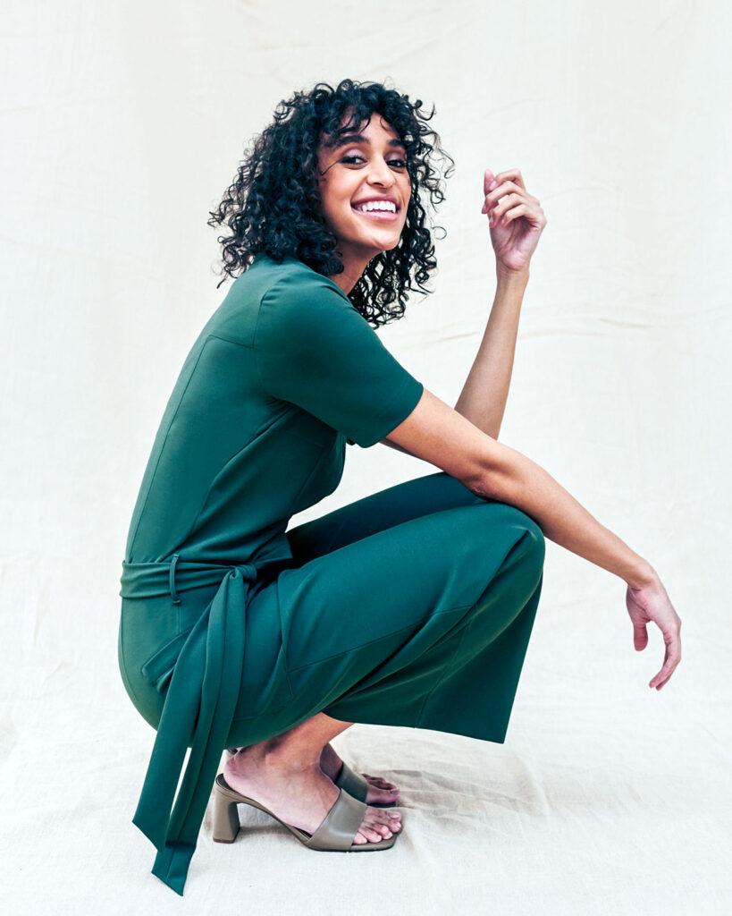 A model squats while wearing a teal green short-sleeved shirt and capri pants.