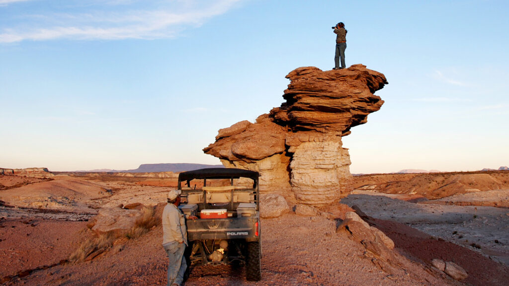 A woman standing on a rock formation in the Texas desert. In the foreground is a man with a jeep.