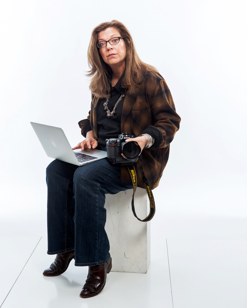 Lori Balton '81 seated, holding a camera and working on a laptop.
