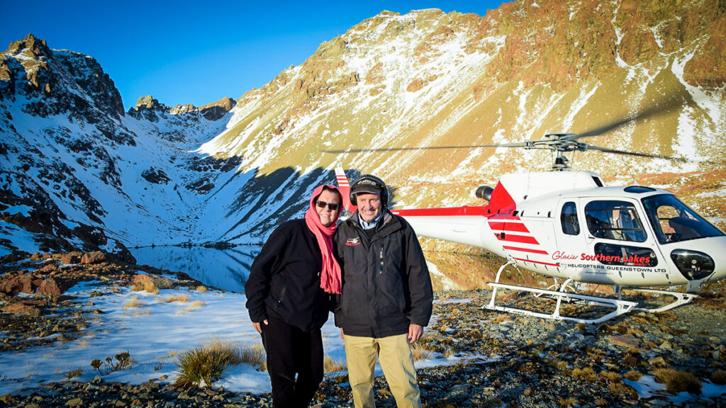 A man and a woman standing in a snowy landscape in front of a helicopter.