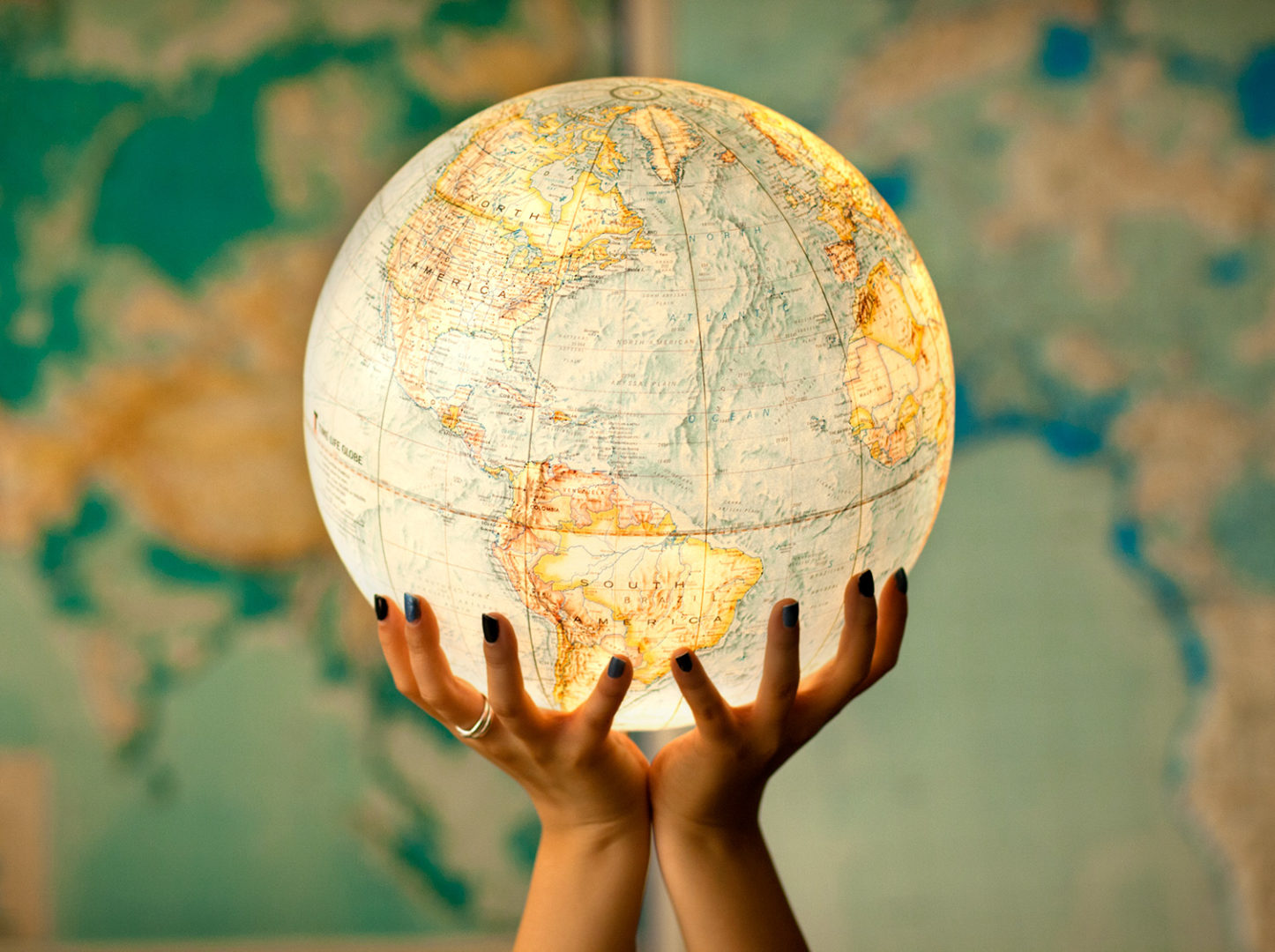 Stock image focusing on hands and globe.