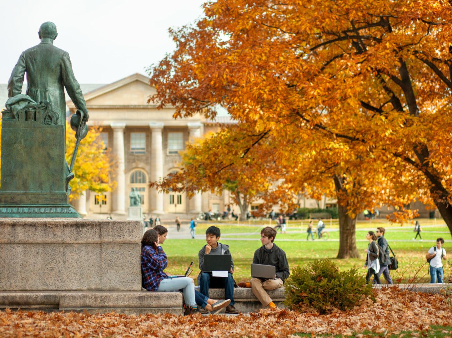 Students study near the statue of Ezra Cornell on the Arts Quad in fall.