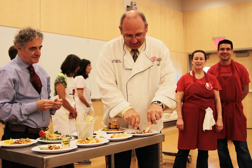 "Giuseppe Pezzotti (left) and Robert White, both chef-instructors in the School of Hotel Administration, judge entrées in the ""Iron Chef"" cooking competition."