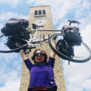 George Epstein, Class of 2015, hoists his bicycle in front of McGraw Tower.