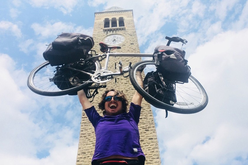 George Epstein '15 hoists his bicycle in front of McGraw Tower.