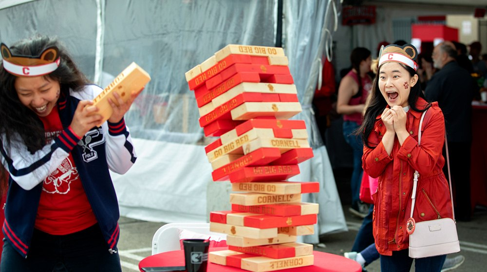 Visitors playing a giant Jenga game at the tailgate tent for alumni and parents.