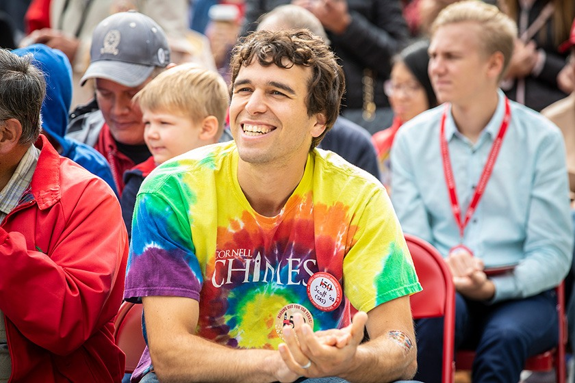 A chimesmaster alumnus in a tie-dyed Cornell Chimes t-shirt