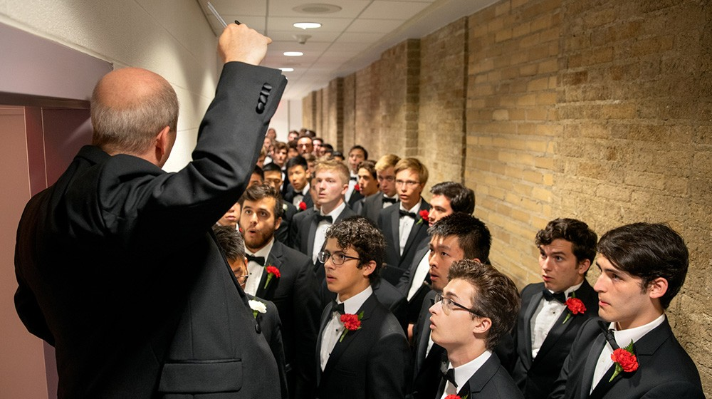 Robert Isaacs, assistant professor and Priscilla Browning Director of Choral Programs, leads members of the Glee Club in a warm up backstage.
