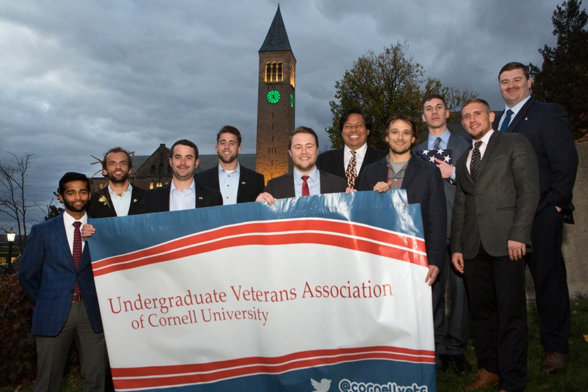 Members of the Undergraduate Veterans Association hold a banner on Ho Plaza..