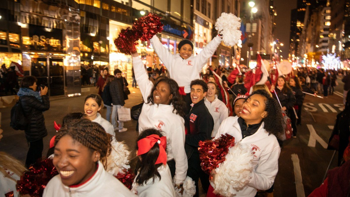 The Cornell cheerleading team parades down Fifth Avenue.