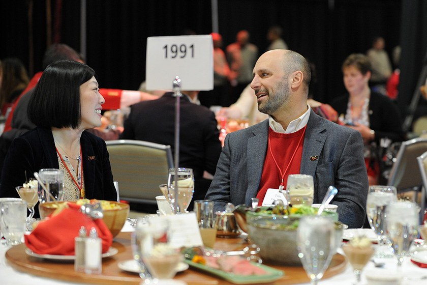 Two alumni, Class of 1991, chat before a meal.