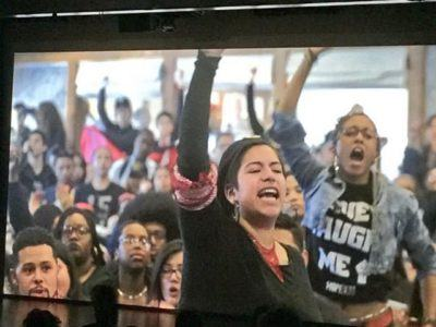 Film screening image. People chanting with arms raised.