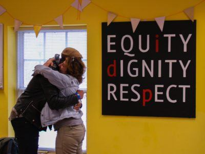 Two people hug in front of a sign that reads, equity, dignity, respect.