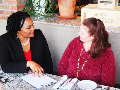 Michelle Courtney Berry at a table, speaking withwith a client.
