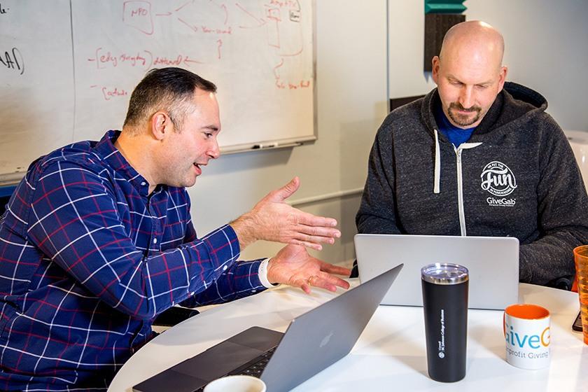 Aaron Godert Charlie Mulligan discuss a problem over laptops.