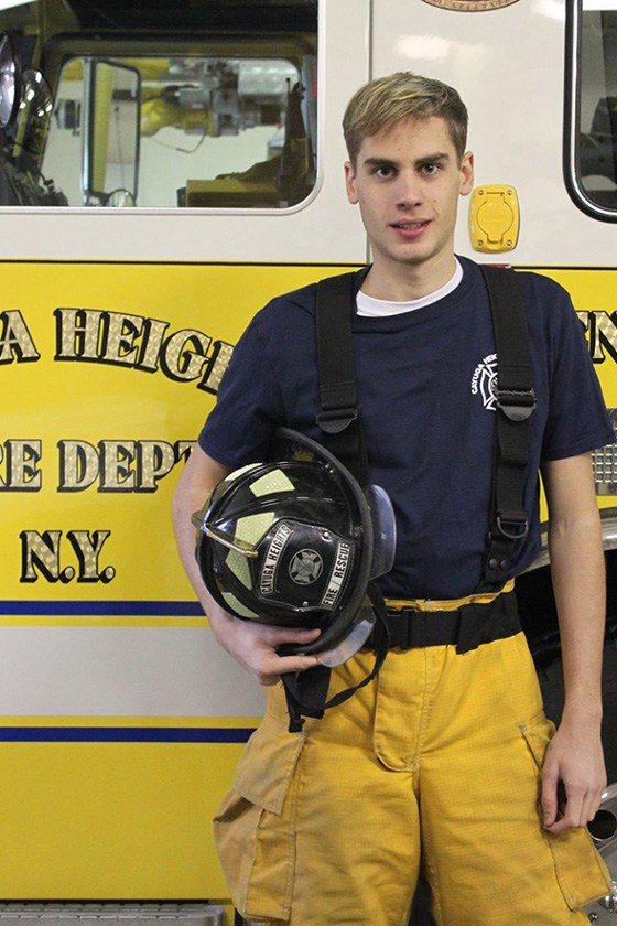 Frank Langrais holding his helmet in front of a Cayuga Heights Fire Department truck.