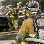 Frank Langrais wearing fire gear, observing other firefighters