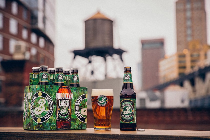 A bottle and pint of Brooklyn Lager, with a cityscape in the background