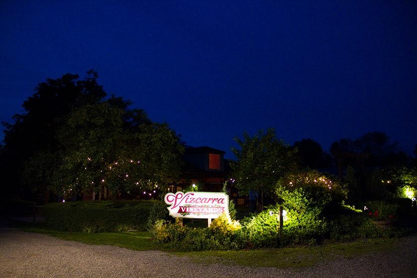 The sign of Vizcarra Vineyards, lit up after sunset