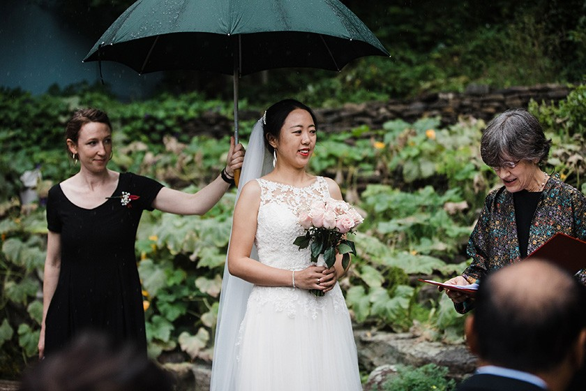 Rachel Conroy holds an umbrella for a wedding client during the ceremony.