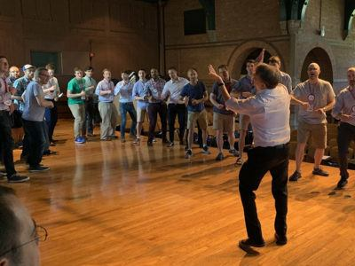 Alumni singers rehearsing in a circle