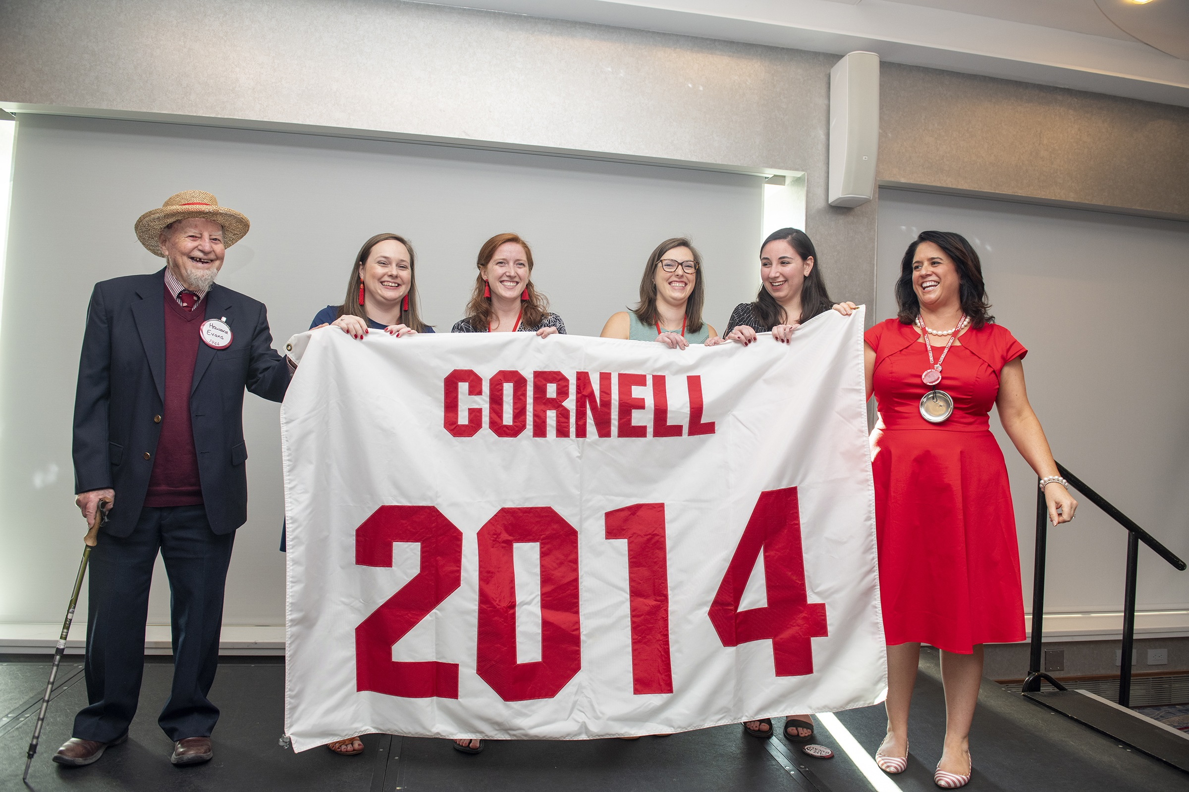 Howard Evans '44 (left) presents a new Class of 2014 banner to Reunion chairs from the Class of 2014