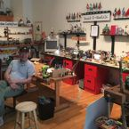 John Galinato '66 sits in the Build It Yourself workshop surrounded by tools, puppets, and contraptions.