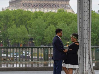 A well-dressed couple on a rainy morning with the Eiffel tower base in the background.