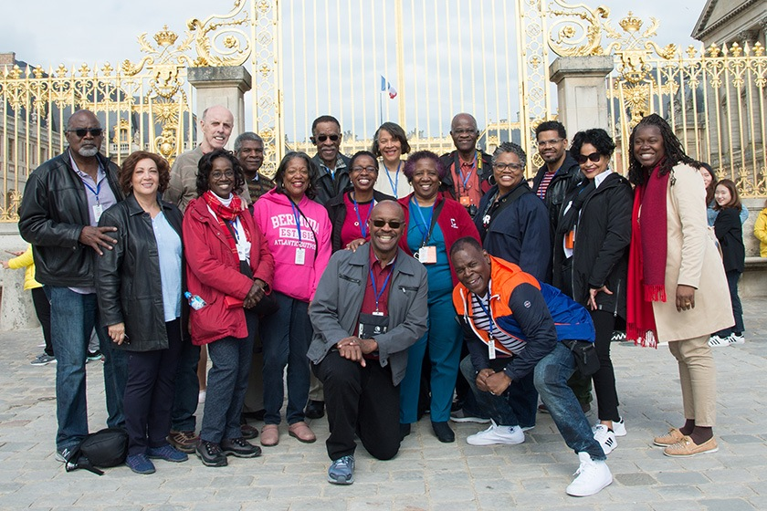 A tour group in front of the golden gates of Versailles.