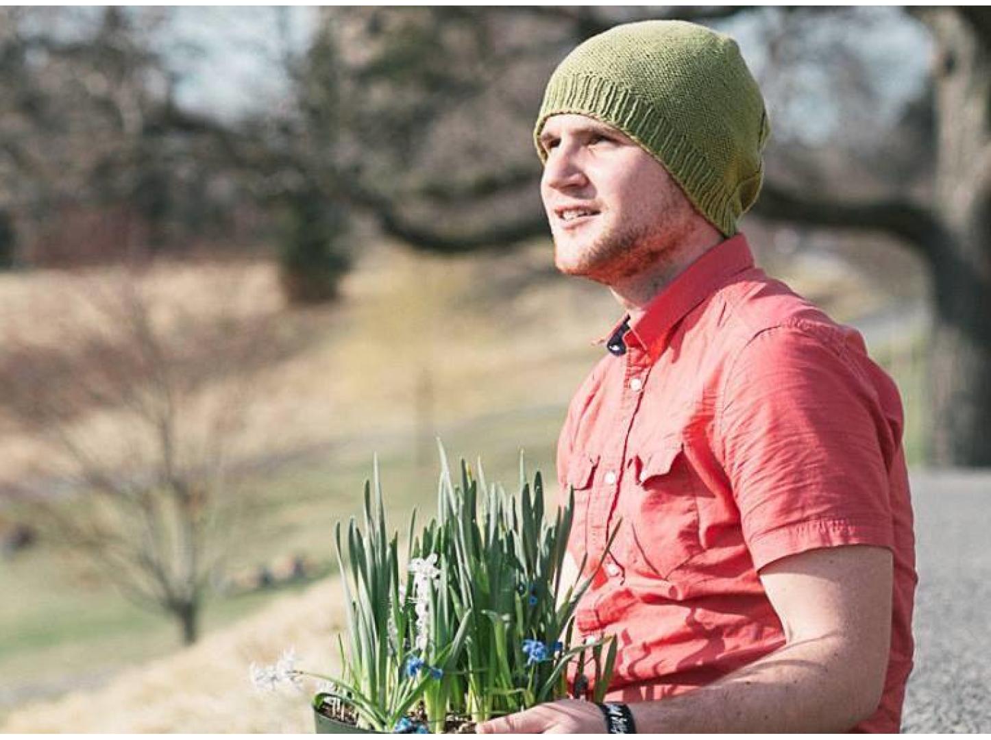 Justin Kondrat '14 sitting on the Slope holding a flower pot