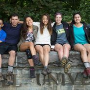Cornell students linking arms on stone wall
