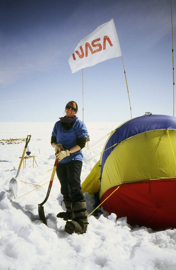 "Ingrid Zabel shoveling snow on the Greenland ice sheet during the summer of 1993. ""We also used shovels to dig pits in the snow so we could view snow layers and ice structures that formed from surface meltwater that percolated down into the snow and then refroze. We were trying to understand how the ice structures scattered energy from our radar signals,"" explains Zabel."
