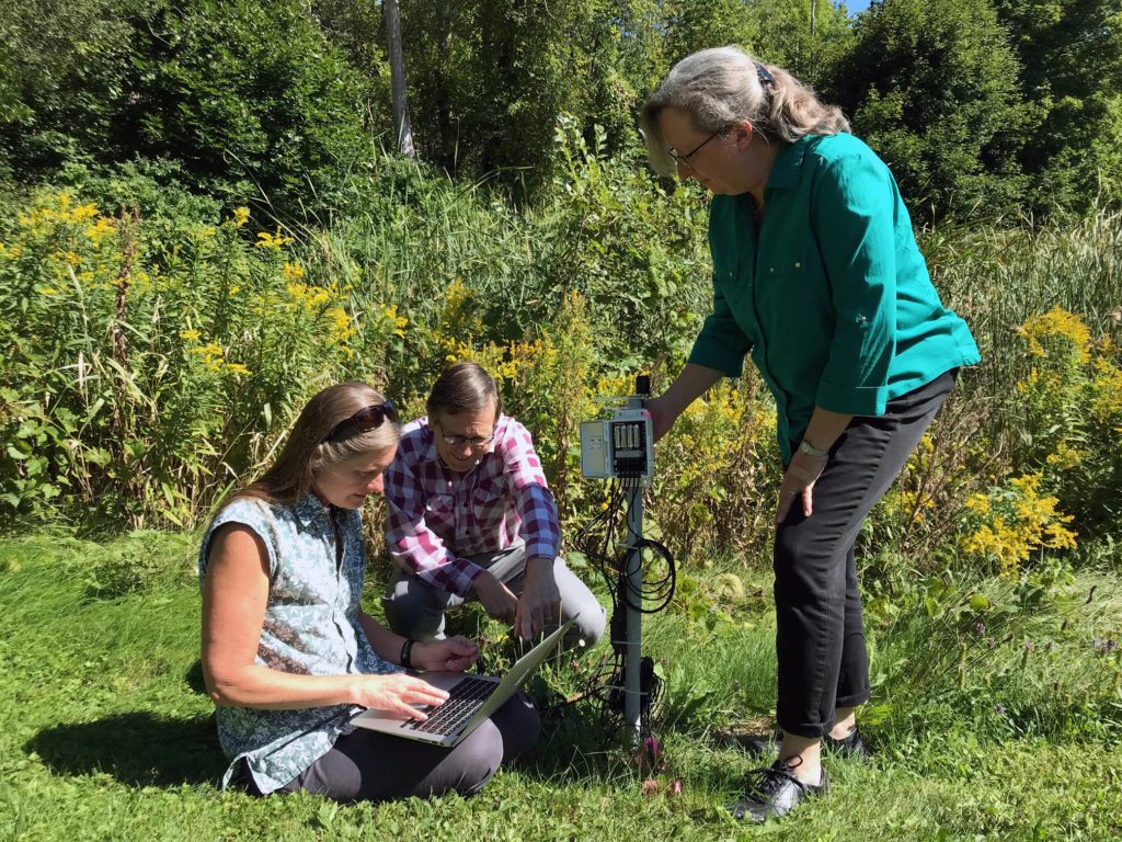 Alexandra Moore, Robert Ross, and Ingrid Zabel (left to right) examine environmental data collected at the Museum of the Earth. The sensors monitor sunlight and the soil temperature at depth, and are used to develop classroom activities to accompany the TFGCC.