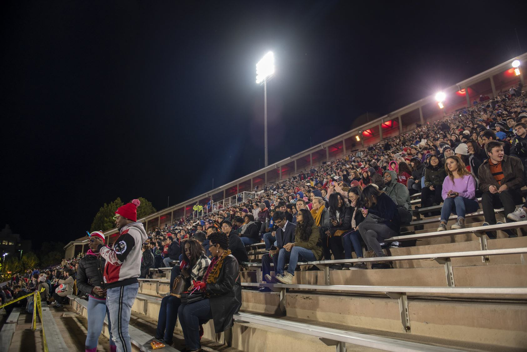 The Schoellkopf Field stands, full of spectators at night.