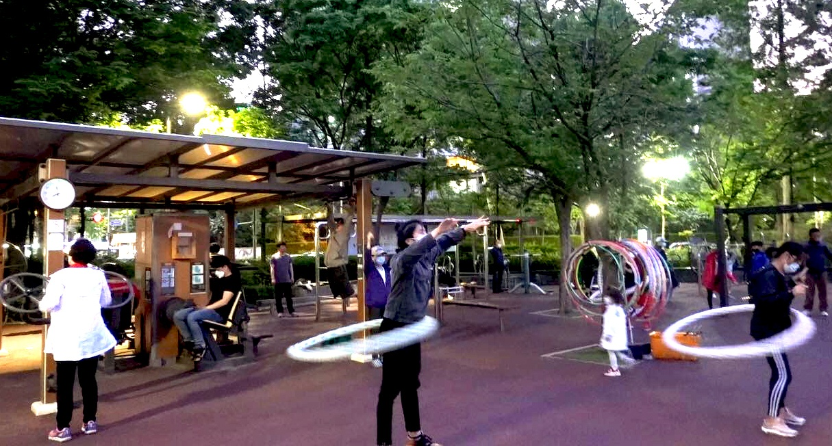 Eric hula-hooping in a public park in Seoul, making sure to wipe down the hoop before and keep two meters away from others.
