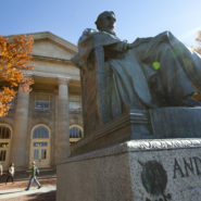 The statue of A D White outside Goldwin Smith Hall in fall.