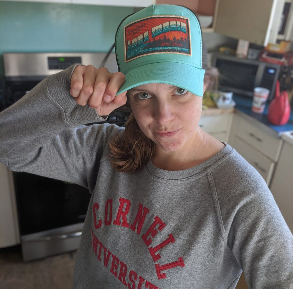"Hannah in a John Prine cap. ""The loss of John Prine hit my family hard, as he has been a constant companion on road trips and family outings. His way of distilling this complicated world provided a sense of comfort,"" she says."