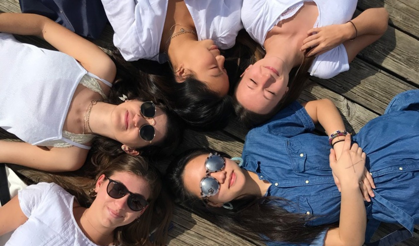 (from bottom left to right) Carson Sheinberg '21, Amanda Cronin '21, Ashlyn Koh '21, Megan Peterson '21, and Savanna Lim '21 (in blue), relaxing on the dock at the Ithaca Farmer's Market.
