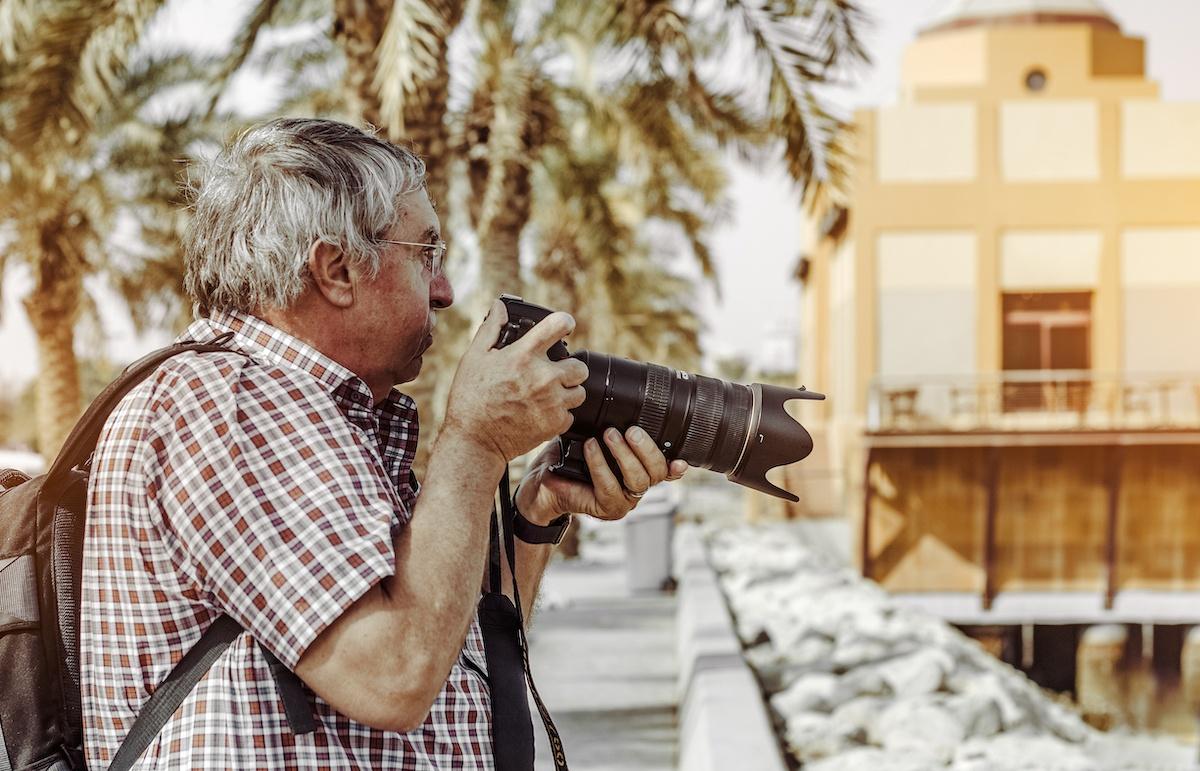 older man taking photos