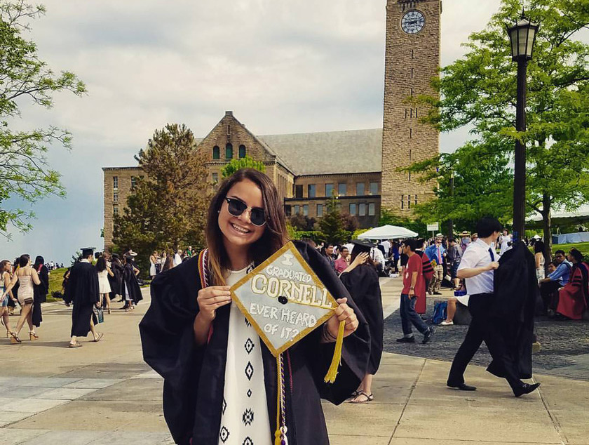 "Camila Salazar on graduation day, in front of the clock tower. Her graduation cap says, ""I graduated CORNELL, ever heard of it?,"" a nod to the infamous Andy Bernard reference to Cornell in The Office."