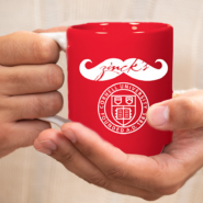 hands holding a red zinck's night mug with mustache and Cornell seal