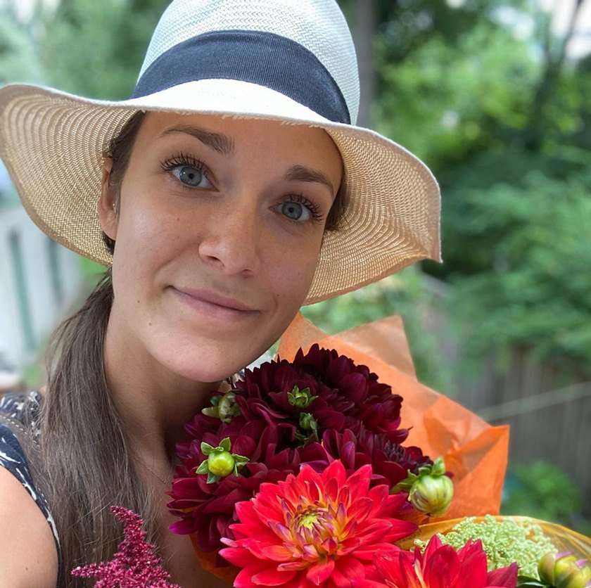 Marta H. Wisniewska enjoying summer weather and summer crops, freshly bought at the Ithaca Farmers' Market.