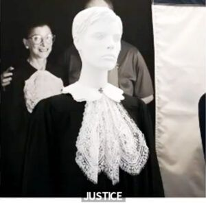 "Photo of RBG with the one of the two judicial collars she contributed to the ""Women Empowered, Fashions from the Front Line"" exhibit."